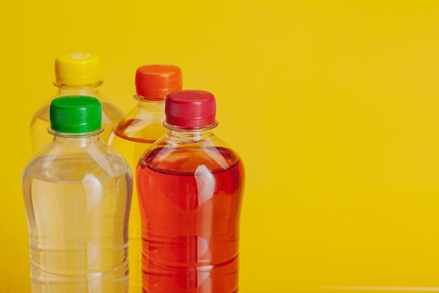 Пластиковая бутылка с напитком на ярко-желтом фоне
