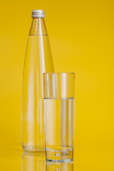 Стакан воды на желтом фоне. здоровый образ жизни