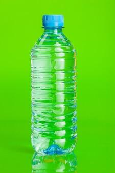 緑色の背景で瓶の中の透明な水