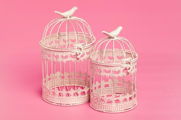 ピンク色の背景にホワイトメタル装飾ケージ
