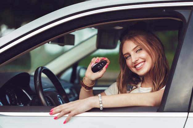 新しい車にキーを保持している若い女性