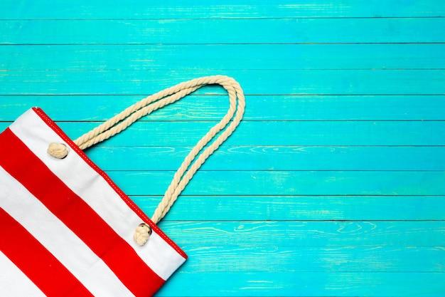Ткань цветной пляжная сумка на ярко-синем фоне деревянных