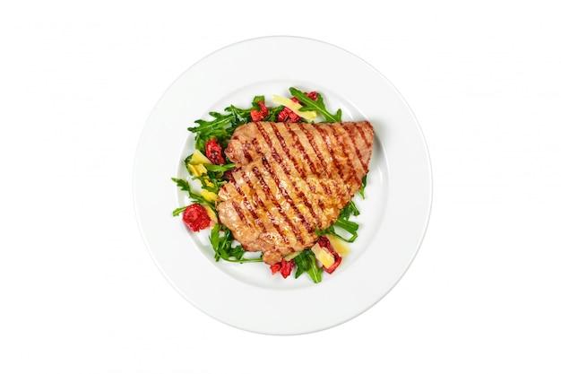 白い背景で隔離のサラダを添えておいしいおいしいポークステーキ