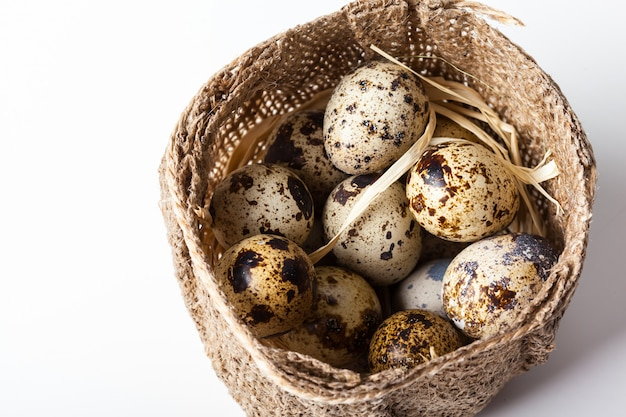Свежие перепелиные яйца на деревянной тарелке крупным планом