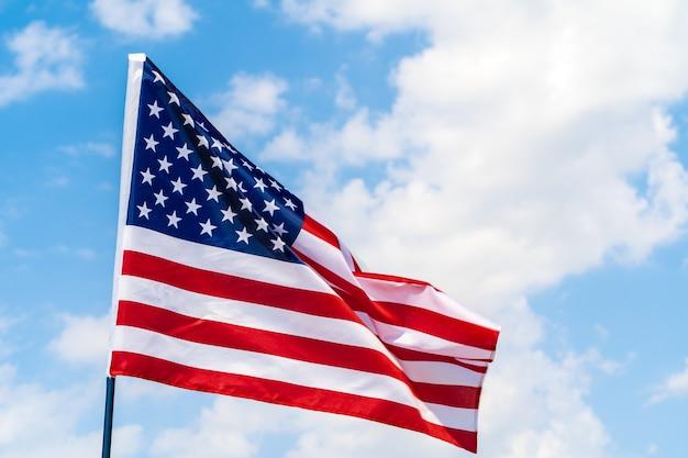 Американский флаг развевается на ветру против голубого неба