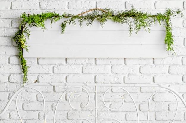 モミの木の枝で飾られたベッドの上の白いレンガの壁に空白の白い木の板ハング