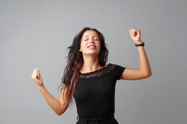 Счастливая молодая женщина показывая знак победы
