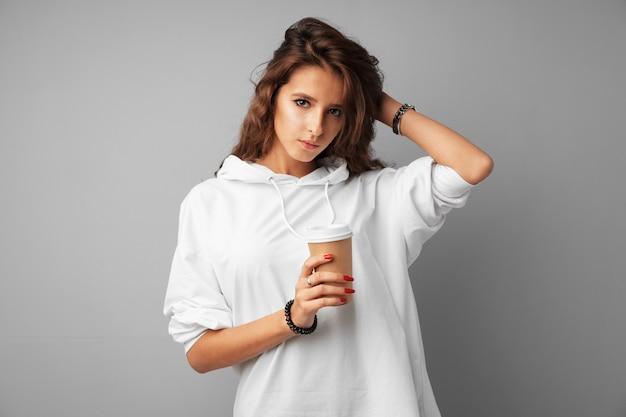 Славная брюнетка молодая женщина держит чашку кофе