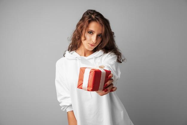 Славная женщина держит в руках красную подарочную коробку