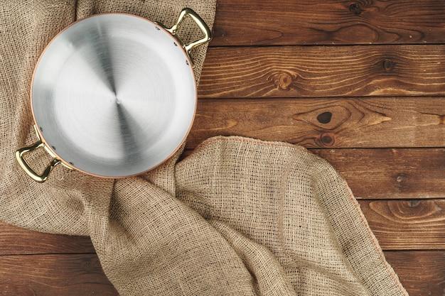 木製テーブルの上の新しい銅鍋、上からの眺め