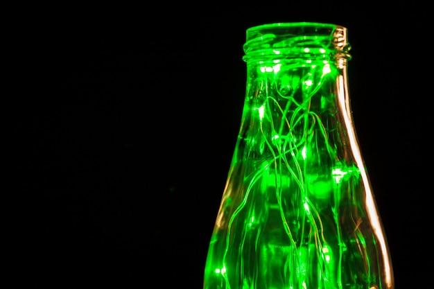 ガラス収納瓶に入れられた電球と緑の花輪