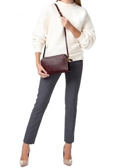 白い背景で隔離のハンドバッグを保持している女性