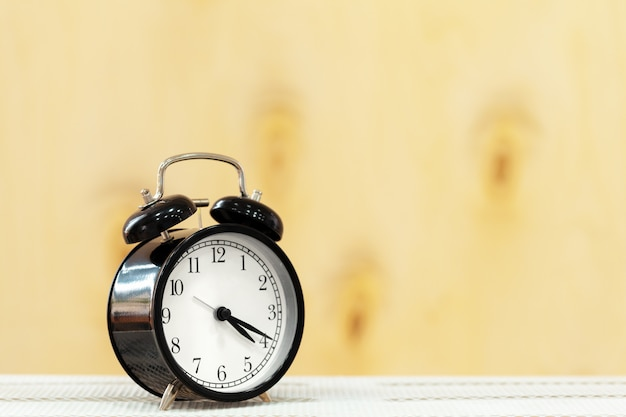 木製のテーブルの上の目覚まし時計をクローズアップ