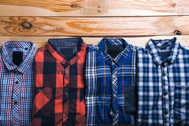 木製の背景を持つ計画で格子縞のシャツ