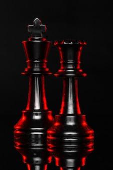 赤いバックライトと暗闇の中でチェスの駒をクローズアップ