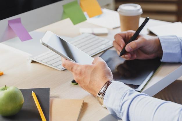 オフィスの机で携帯電話を使用して忙しいビジネスの男の手
