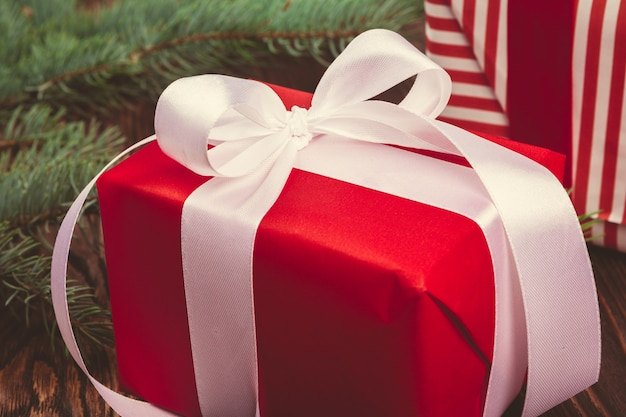 クリスマスプレゼントと木製のテーブル、トップビューで松の木の枝
