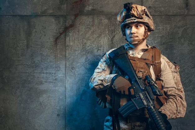 ピストルとアサルトサービスライフルで武装した、迷彩服とヘルメットの完全装備の軍隊兵士