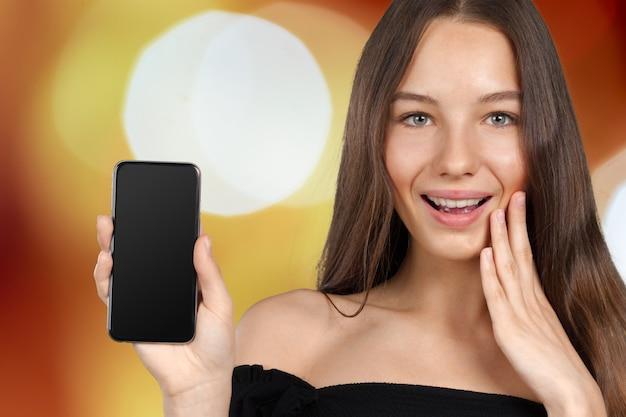 Портрет молодой модной женщины, держащей смартфон