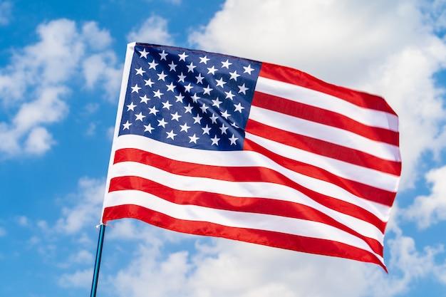 Американский флаг на флагштоке развевался на ветру против белых облаков
