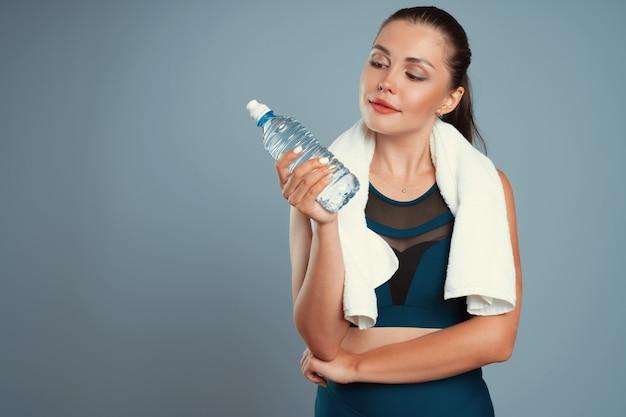 ミネラルウォーターのボトルを手に持ったスポーティな女性に合う