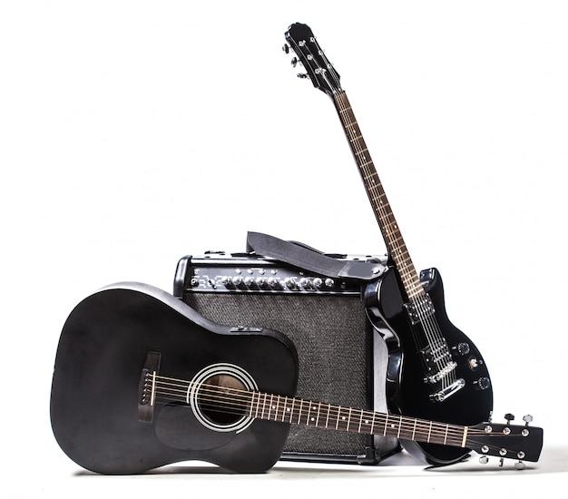 黒のエレキギターと白で隔離されるアコースティックギター
