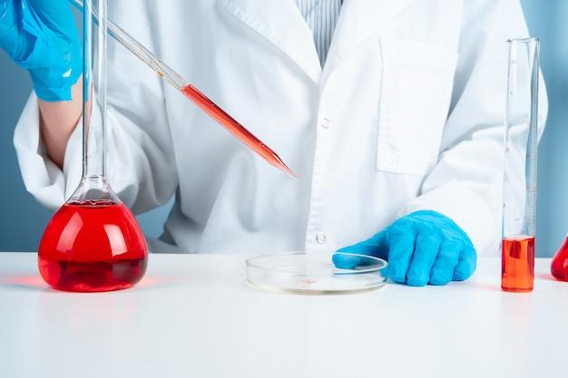 臨床検査室で研究を行う試験管を持つ若い科学者、職場の専門科学の専門家、