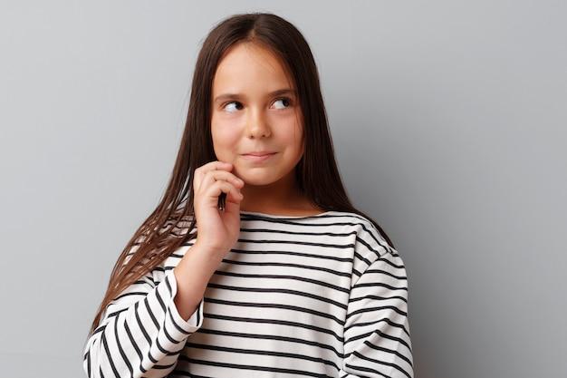 立っている思考の若い女の子の画像
