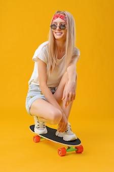Довольно счастливая женщина небрежно одетая сидит на своем скейтборде