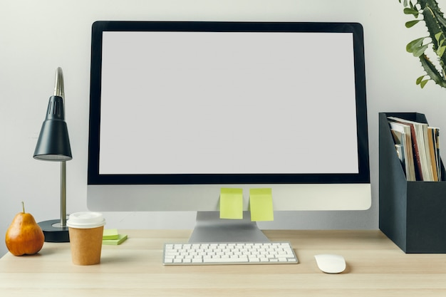 備品のオフィステーブルの上のモックアップの白い画面とコンピューターモニター