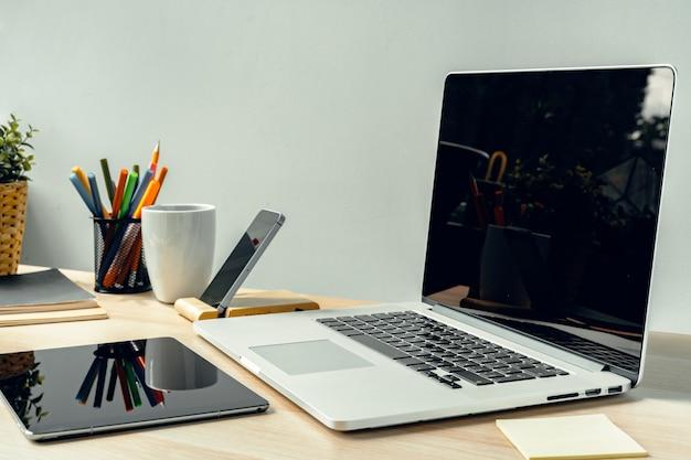 事務用品と作業テーブルの上の明るい部屋でノートパソコン