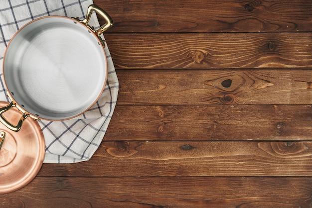 木製の表面テーブルに新しい銅鍋、上からの眺め