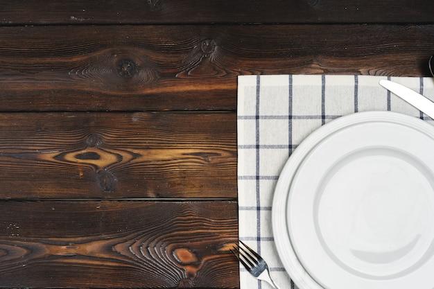 暗い木製の表面にプレートを設置したテーブル