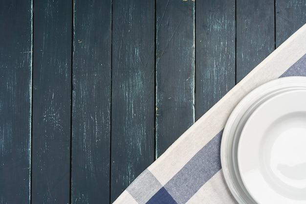 Сервировка стола с тарелками на темной деревянной поверхности