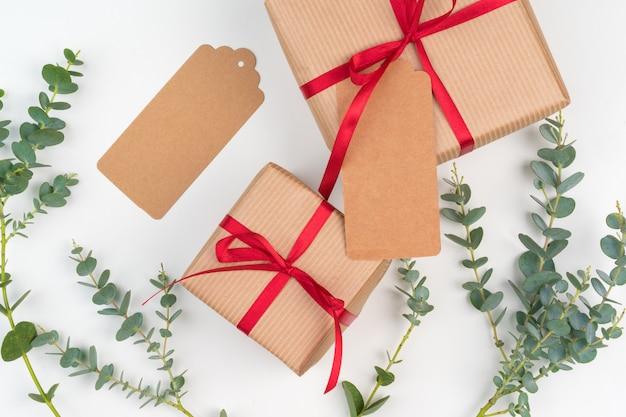 Подарочные коробки, упакованные в крафт-бумагу с простым декором из зеленых веток растений