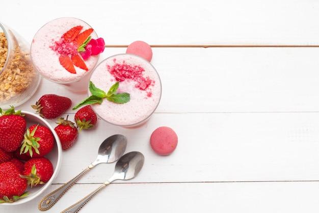 Здоровый завтрак с йогуртом, мюсли и клубникой на белой деревянной поверхности вид сверху