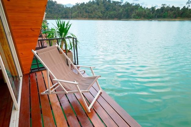 アジアの川の上の木製の表面デッキで屋外のパティオ家具