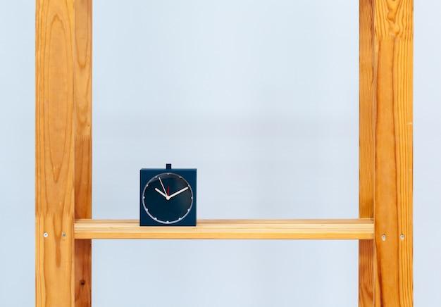目覚まし時計と青に対するオブジェクトの木製の棚