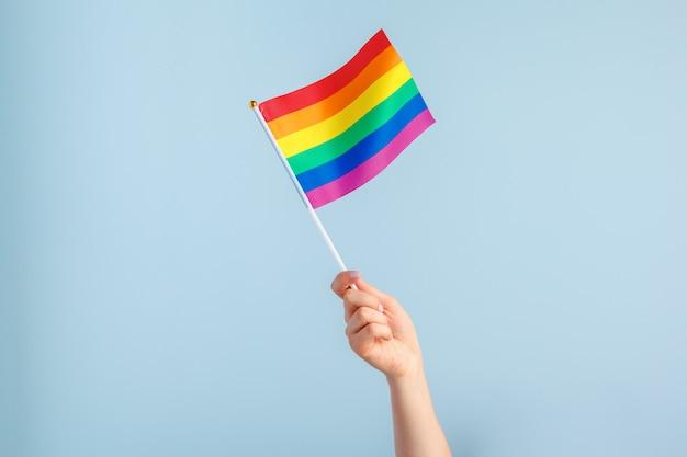 Гей флаги в женской руке на сером