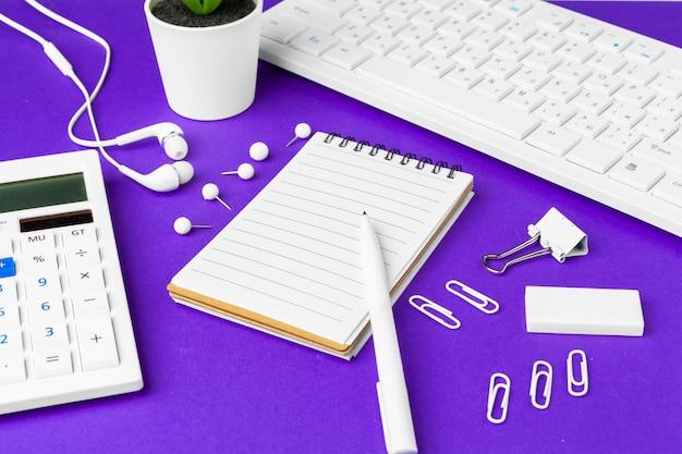 Состав офисных предметов образа жизни на фиолетовый, компьютерная клавиатура канцелярских принадлежностей на столе в офисе