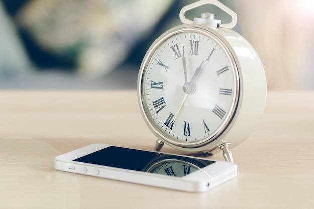 木製のテーブルに携帯電話付き目覚まし時計