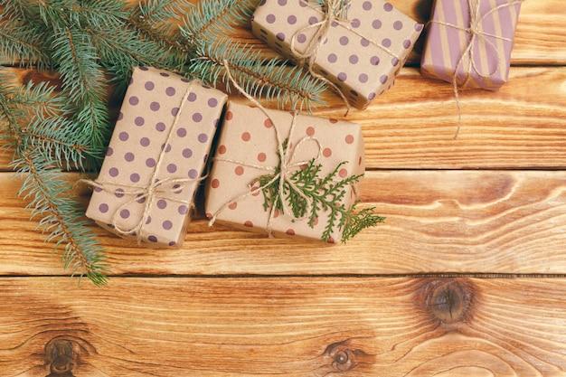 木製の表面にモミの木の枝とのクリスマスプレゼント