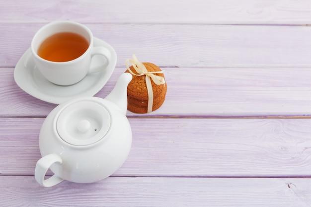 ライラックの木製の表面上のクッキーとお茶のカップ