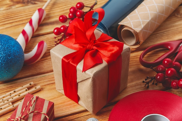Упаковка подарочных коробок с оборудованием и декорирование предметов на деревянной поверхности