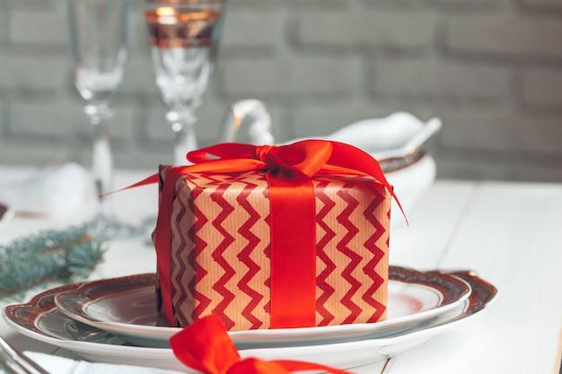 装飾の美しい赤いクリスマステーブルの設定をクローズアップ