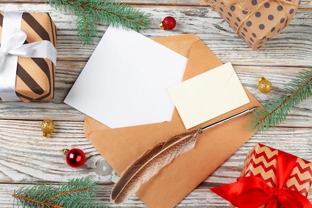 サンタクロースコンセプト、休日の装飾と木製の背景の紙への手紙の平面図