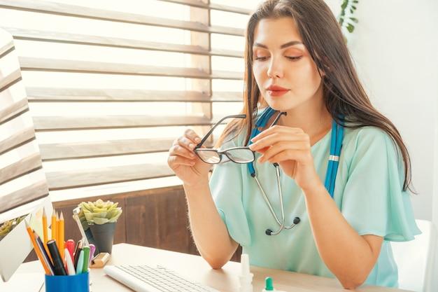 Хорошо выглядящая женщина-врач сидит за своим столом в медицинском кабинете