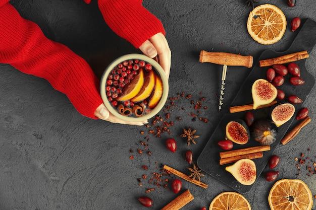 グリューワインのカップを保持している暖かいセーターの女性の手
