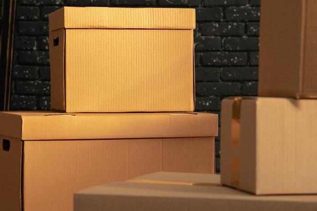 Стопка картонных коробок в пустой комнате на фоне черной кирпичной стены