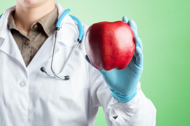 Стоматолог держит спелое яблоко